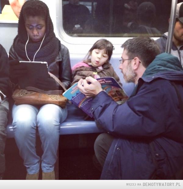 Fotka na wyginięciu:Ojciec czyta książkę dziecku w metrze –